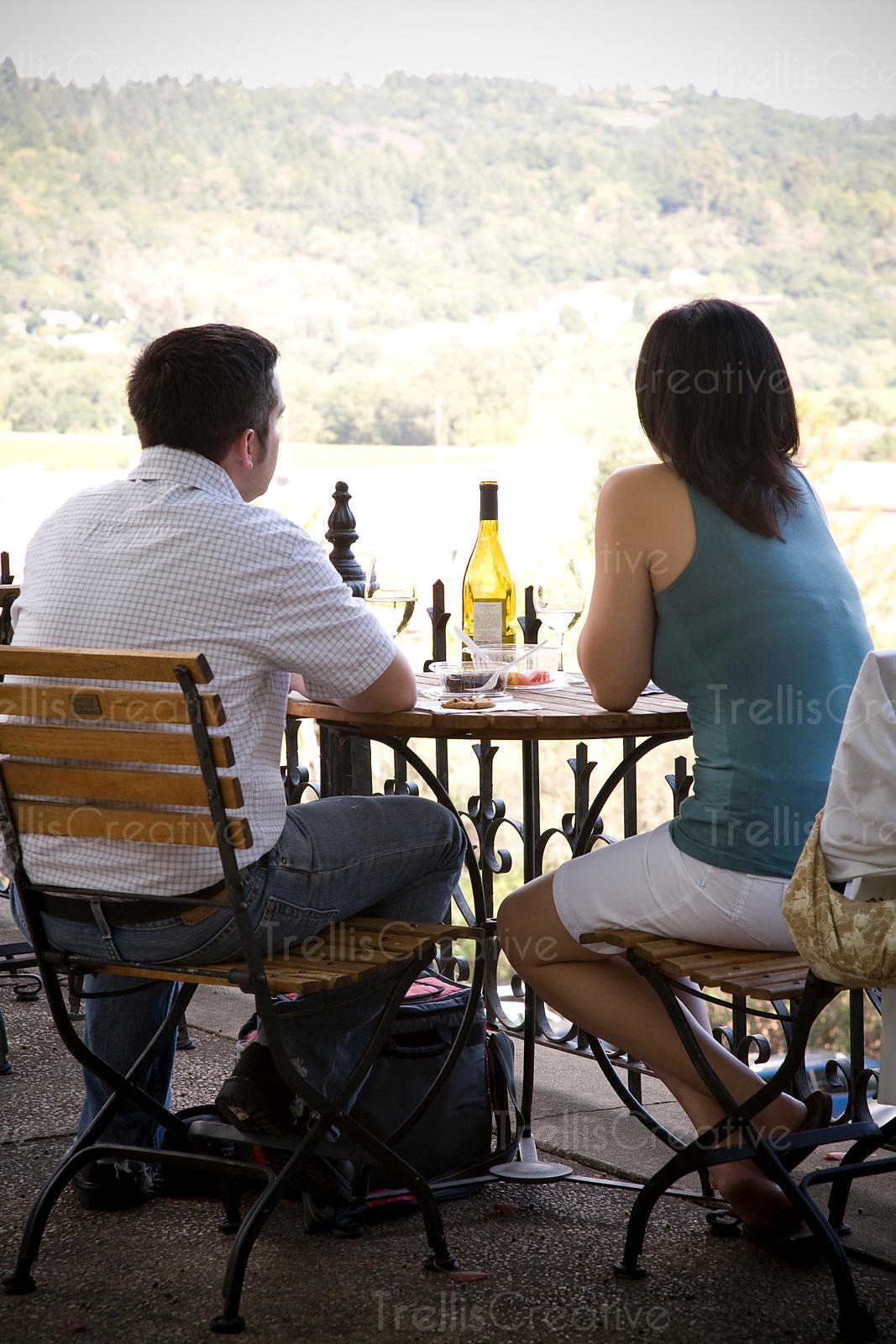 A young couple enjoy a bottle of wine outside