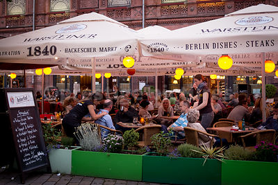 Two Men having shoulder massages in an Outdoor Restaurant in Hackerscher Markt, Berlin