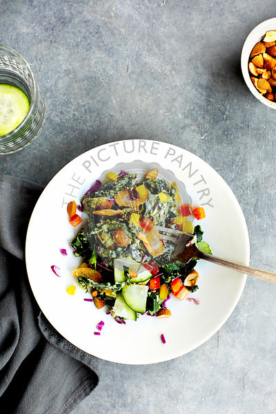 Kale Vegetable Salad with Parsley Pesto Vinaigrette.  Photographed on a grey background.