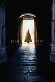 An atmospheric image of cloaked woman rushing out of an old building.