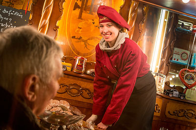 Smiling young woman selling chocolates and biscuits at a Hamburg Christmas Market