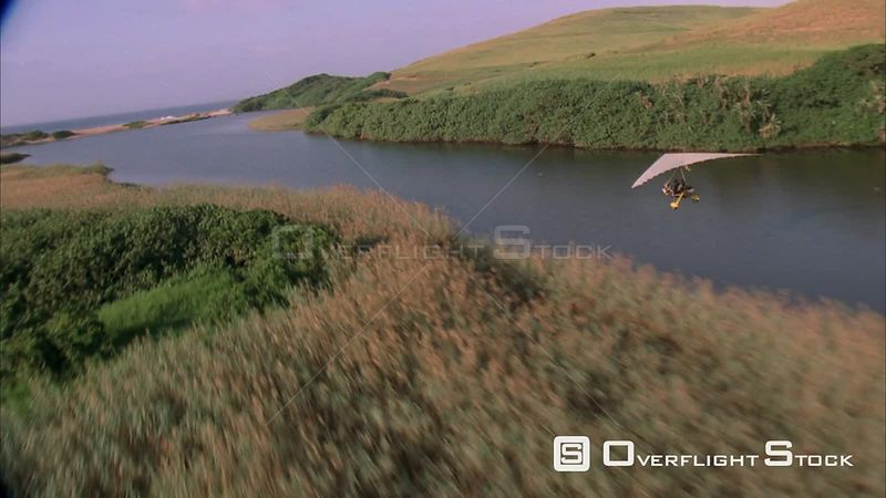 Air to air shot of two microlights flying along a river with lush green banks on either side, moving towards the sea. KwaZulu...