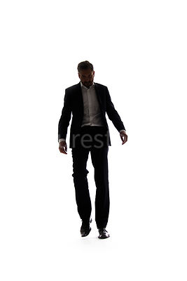 A mystery man in a suit, walking towards camera, in semi-silhouette – shot from low level.
