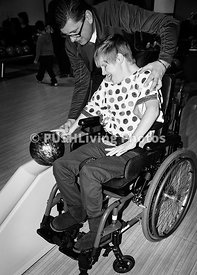 Girl in a wheelchair with her father at a bowling alley