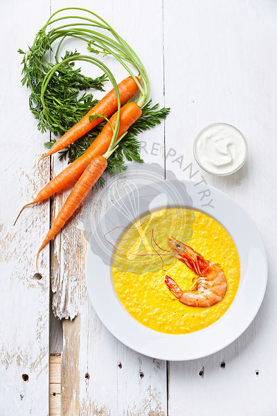 Carrot soup with shrimp on white wooden background