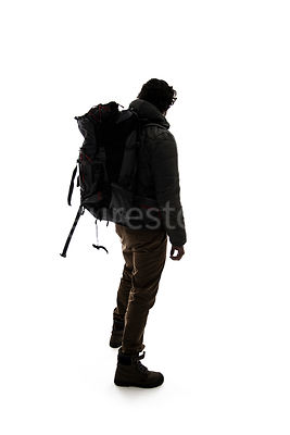A man in outdoor clothing with a backpack, from behind, in silhouette – shot from eye level.