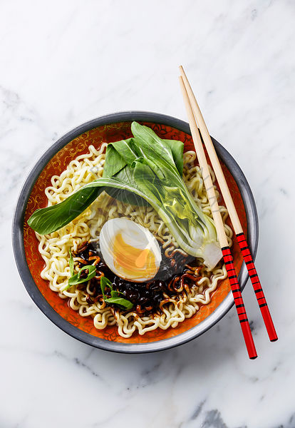 Ramen Asian noodles with egg and pak choi cabbage on white marble background