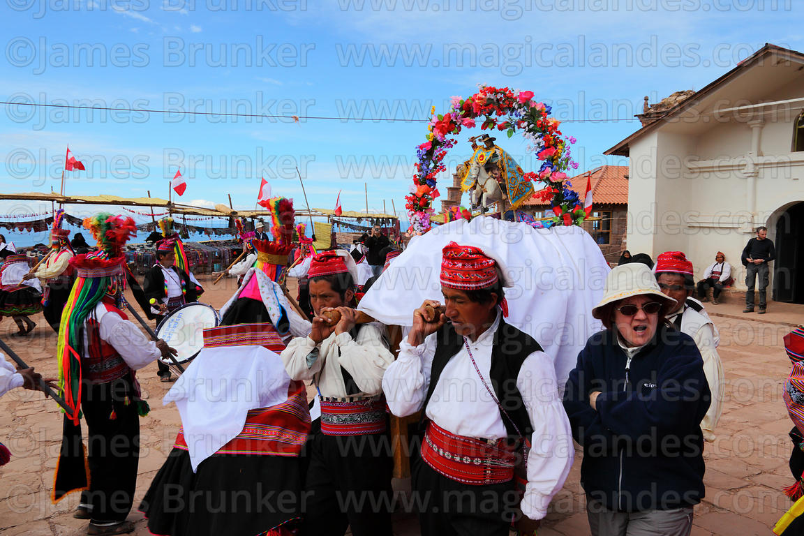 Locals parade with figure of San Santiago after mass , Taquile Island , Peru