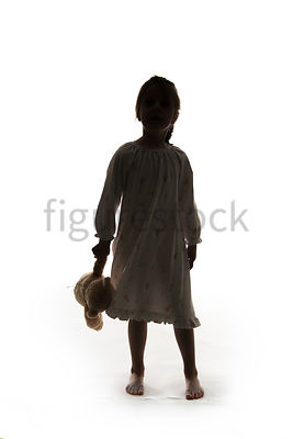 A Figurestock image of a little girl, in silhouette, standing in a night dress holding a teddy bear – shot from eye level.
