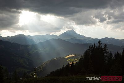 Dramatic light from clouds over valley in the italian alps