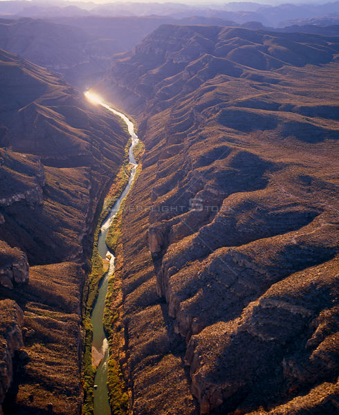 Aerial view of Rio Grande passing through the Boquillas Canyon with the Chisos Mountains and Big Bend National Park in the ba...