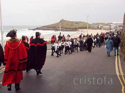 the St Ives Feast procession passes along side Porthmoer  Beach