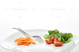 Dish with small portion of salad and olive oil on white background