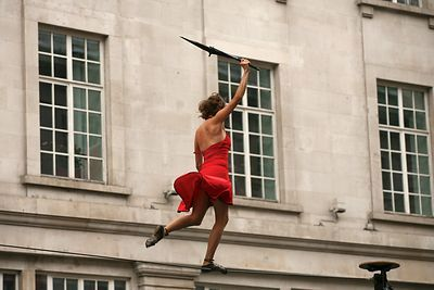 Woman with Red Dress blowing up walks a tightrope holding an umbrella in Regent Street, London