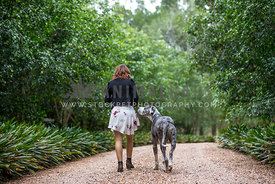A girl and her dog walking down a tree lined path