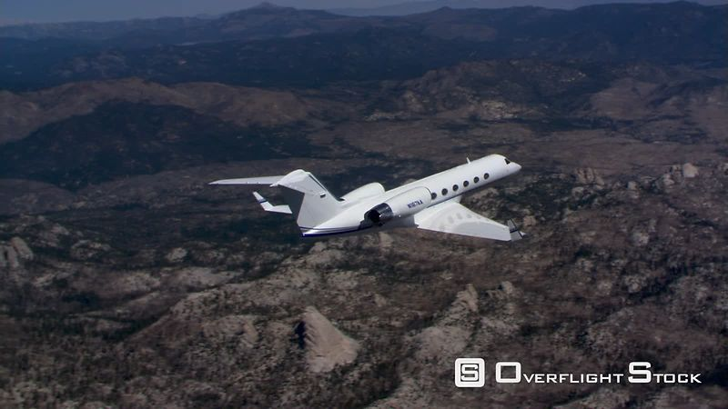Business jet in flight, side and rear air-to-air view