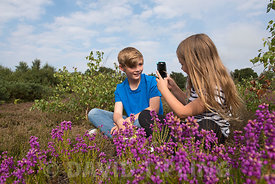 Young girl taking picture of her brother on smart phone  on heath Kelling Norfolk UK
