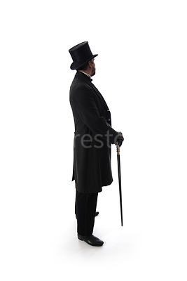 A Victorian man standing in a hat and coat, with a cane, In semi-silhouette – shot from eye level.
