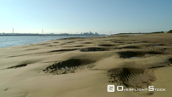 Drone flies low over New Brighton Beach to reveal the skyline of Liverpool on a sunny summer morning