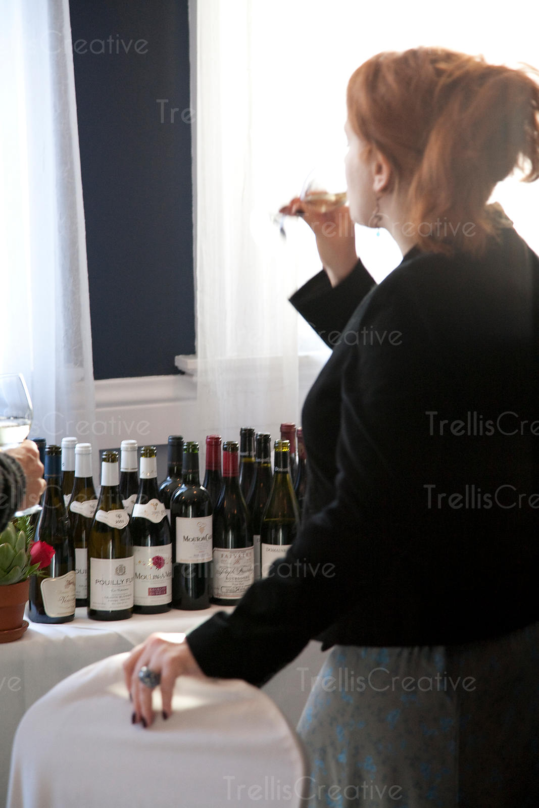 Young redheaded woman drinking wine