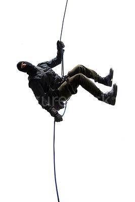 A masked mystery man abseiling down a rope.