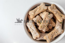 bowl of homemade dog biscuits on white background