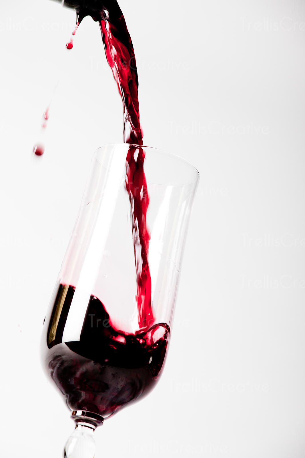 Spilling red wine into a glass causing a splash