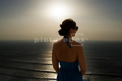 An atmospheric image of  a woman looking out to sea, from a cliff top.