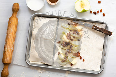 Prepartion of apple studel, sliced apples, cinnamon and sugar on a pastry sheet resting on a baking tray with a knife.