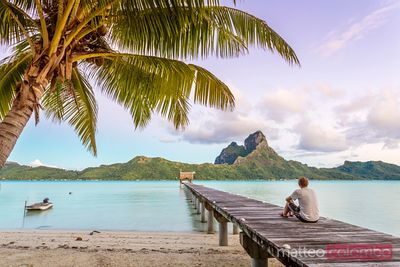 Man enjoying sunrise in the lagoon of Bora Bora, French Polynesia
