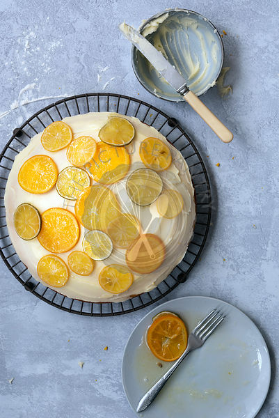 A round homemade orange cake spread with butter icing and decorated with candied lemon, lime and oranges slices.