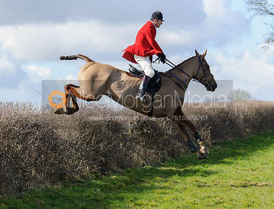 Adam Cooke jumping a hedge behind Ladywood Lodge