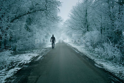 An atmospheric image of a mystery man walking down an empty, misty country road, surrounded by hoar frost covered trees and hedgerow, in winter.