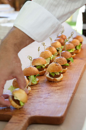 A man's hand reaches for a beef slider at an outdoor party