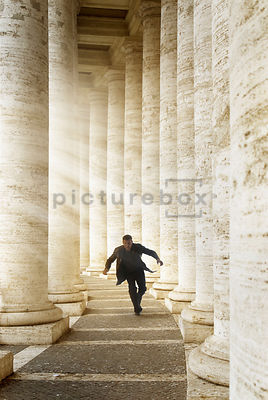 An atmospheric image of a mystery man running through the columns at Saint Peter's Square, Rome, Italy.