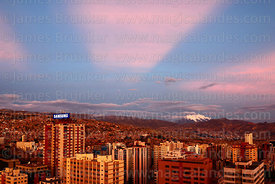 High rise buildings in Sopocachi and anticrepuscular rays at sunset, Mt Illimani in distance, La Paz, Bolivia