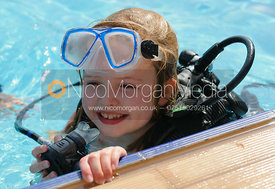 A blonde girl learning to scuba dive with an instructor, Salalah, Oman