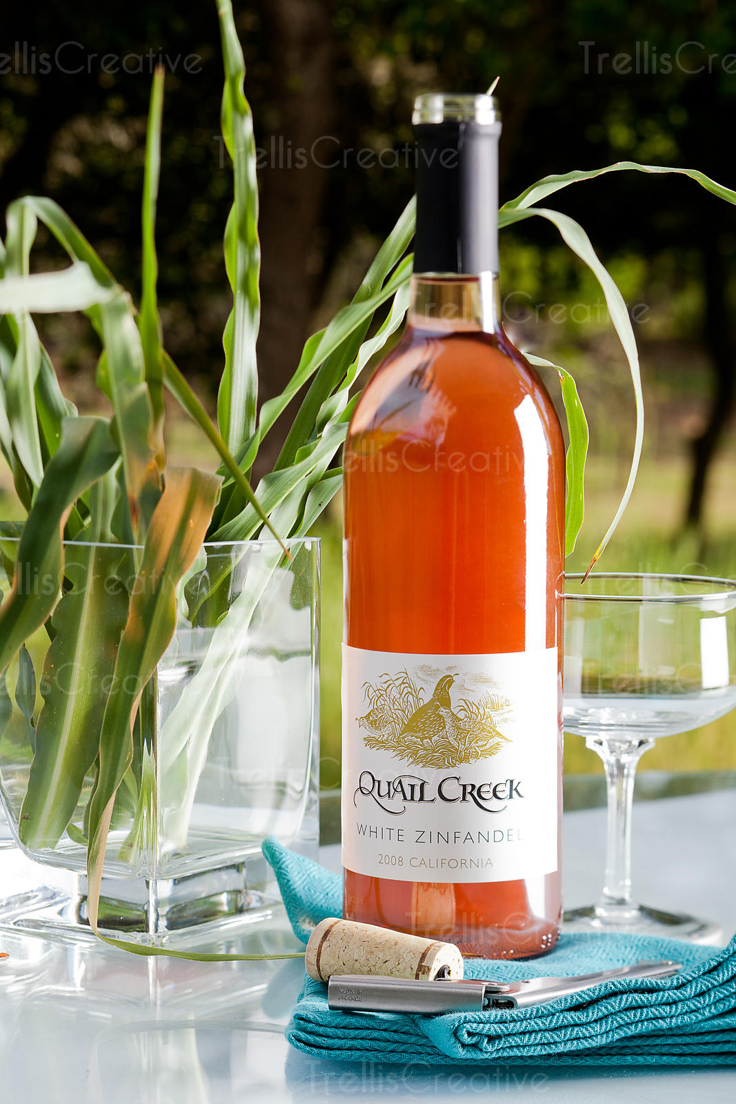 An opened bottle of rose wine on an outdoor patio table