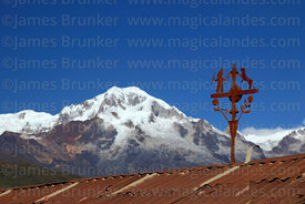 Rusted metal cross on roof of house near Sorata and Mt Illampu, Bolivia