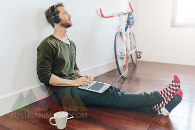 Pensive man with headphones and laptop sitting on the floor at home