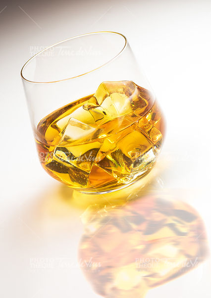 Glass of whiskey with ice on white background