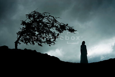 An atmospheric image of a mystery woman in a dress, wondering the moor, on a stormy night.