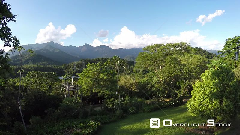 Aerial shot ascending from a garden to reveal an area of the Atlantic Forest, Reserva Ecologica de Guapiacu, Rio de Janeiro, ...