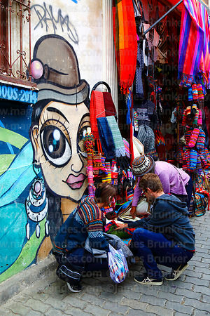 Cholita street art and tourists browsing textiles hanging outside shop in tourist market, La Paz, Bolivia