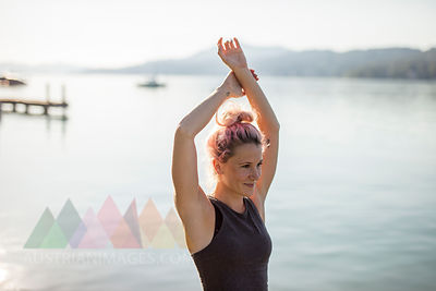 Woman in sportswear stretching at a lake