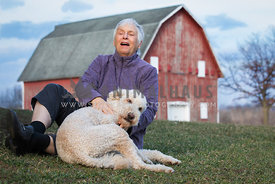 Friendly senior lady having fun with cute golden doodle dog outside in front f red barn.