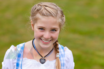 Germany, Luneburger Heide, portrait of smiling blond girl wearing dirndl