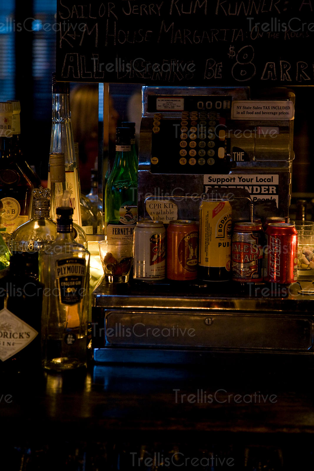Bar's old-fashioned cash register adorned with beer bottles and cans