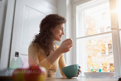 Young woman at table eating from cereal bowl
