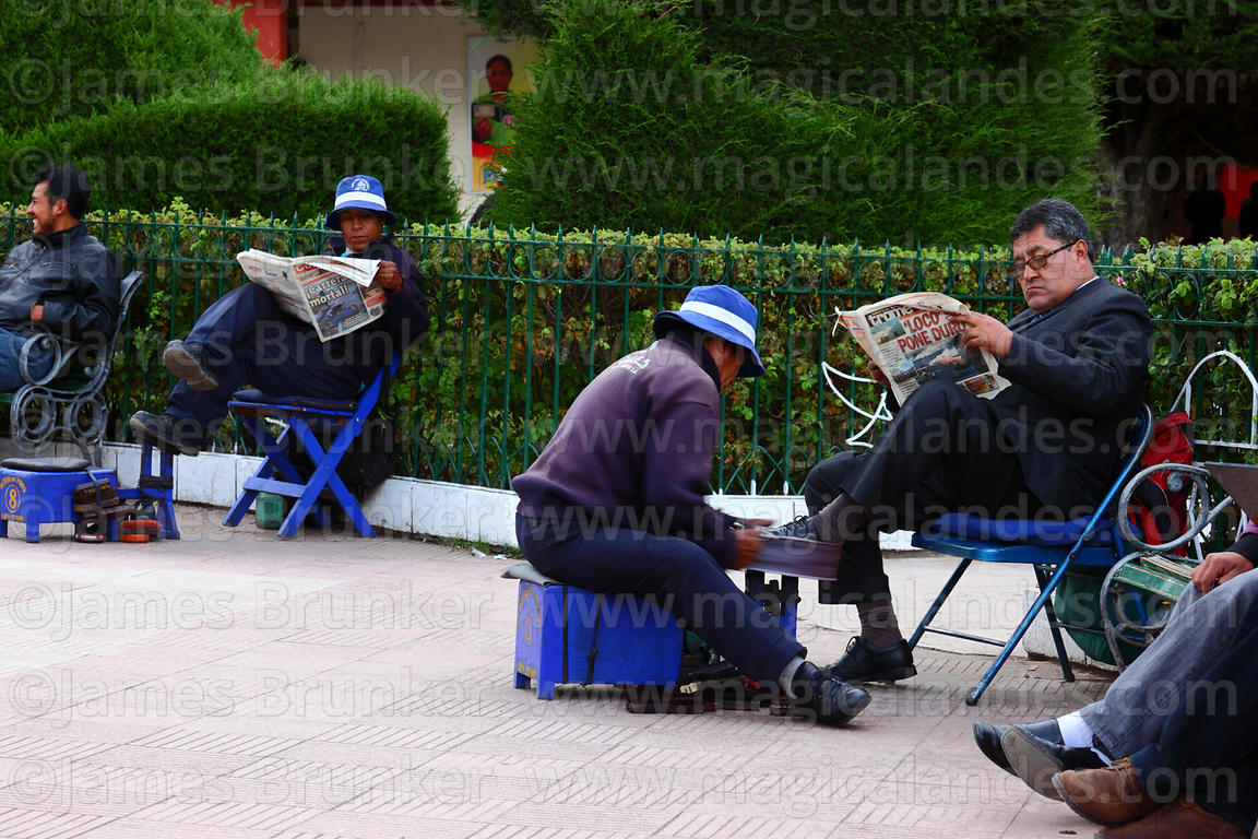 Shoe shiner at work in Plaza de Armas, Puno, Peru